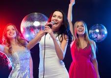 Tres mujeres sonrientes que bailan y que cantan Karaoke Imágenes de archivo libres de regalías