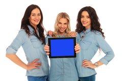 Tres mujeres sonrientes que le muestran la pantalla de una tableta Fotos de archivo