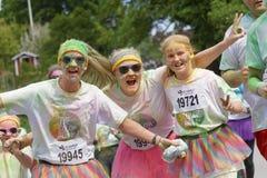 Tres mujeres sonrientes y la muchacha cubiertas con color verde sacan el polvo Imagenes de archivo