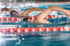 Tres nadadores de sexo masculino que hacen estilo libre en diversos carriles de natación foto de archivo