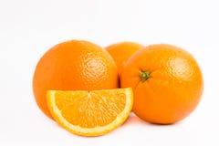 Tres naranjas jugosas frescas y un lóbulo de la rebanada aislados en el fondo blanco fotografía de archivo