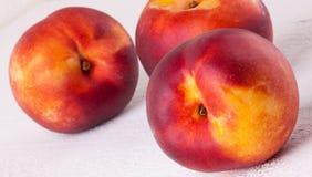 Tres nectarinas jugosas maduras frescas sabrosas foto de archivo