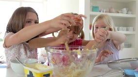 Tres niñas que hacen la torta junto almacen de video