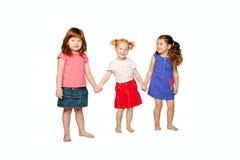 Tres niñas que llevan a cabo las manos. Imagen de archivo libre de regalías