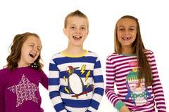 Tres niños adorables que ríen los pijamas de la Navidad que llevan Fotos de archivo libres de regalías