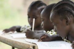 Tres niños africanos que aprenden en la escuela al aire libre fotos de archivo libres de regalías