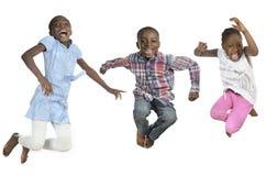 Tres niños africanos que saltan arriba Imagen de archivo libre de regalías