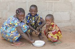 Tres niños africanos que se sientan al aire libre comiendo el arroz en África Fotografía de archivo libre de regalías