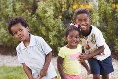 Tres niños afroamericanos en un jardín que mira a la cámara Foto de archivo