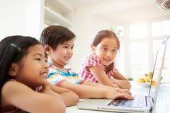 Tres niños asiáticos que usan el ordenador portátil en casa Foto de archivo libre de regalías