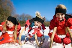 Tres niños con el trineo largo en la nieve Foto de archivo libre de regalías