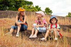 Tres niños con la mochila que se sienta en el sendero en el m Fotos de archivo