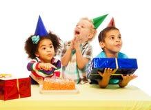 Tres niños con la torta de cumpleaños y los peresents Fotografía de archivo libre de regalías