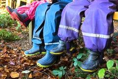 Tres niños con las botas de goma Fotografía de archivo
