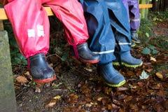 Tres niños con las botas de goma Foto de archivo libre de regalías