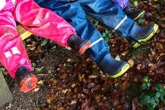 Tres niños con las botas de goma Imagen de archivo