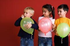 Tres niños con los globos Imagen de archivo libre de regalías