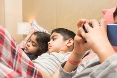 Tres niños con sus artilugios electrónicos en la hora de acostarse imagenes de archivo