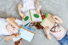 Tres niños de estudiantes con los libros Preparación para los exámenes Th Imagen de archivo