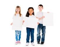Tres niños divertidos que llevan a cabo los espacios en blanco de papel en manos Imagen de archivo libre de regalías