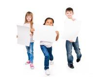 Tres niños divertidos que llevan a cabo los espacios en blanco de papel en manos Foto de archivo