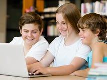 Tres niños en biblioteca fotografía de archivo libre de regalías