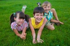 Tres niños en hierba imagen de archivo libre de regalías