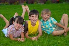 Tres niños en hierba Imágenes de archivo libres de regalías