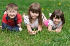 Tres niños en la hierba Imagenes de archivo