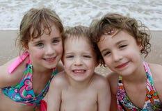 Tres niños en la playa Fotos de archivo libres de regalías