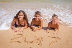 Tres niños en la playa con la muestra del Año Nuevo 2017 Imágenes de archivo libres de regalías