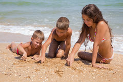 Tres niños en la playa en la arena Foto de archivo