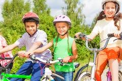 Tres niños en los cascos que se sientan en las bicis Fotos de archivo libres de regalías