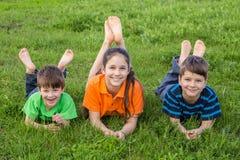 Tres niños en prado del verde de la primavera Foto de archivo libre de regalías