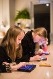 Tres niños en un restaurante usando iPads Fotografía de archivo