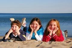 Tres niños en una playa Fotos de archivo