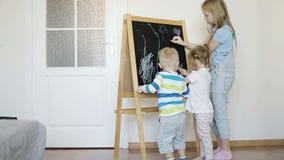 Tres niños están dibujando con los creyones en un tablero de madera almacen de metraje de vídeo