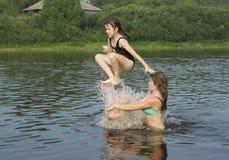 Tres niños felices que juegan y que saltan en el agua Imagen de archivo libre de regalías
