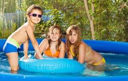 Tres niños felices que se divierten en la tina en la yarda fotografía de archivo libre de regalías