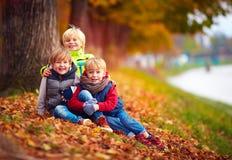 Tres niños hermosos, amigos junto en parque del otoño fotografía de archivo