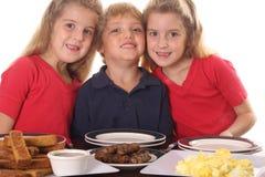 Tres niños jovenes en el desayuno Imágenes de archivo libres de regalías
