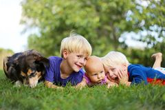 Tres niños jovenes que se relajan afuera con el perro casero imágenes de archivo libres de regalías