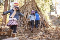 Tres niños juegan fuera del refugio hecho de ramas en un bosque Foto de archivo libre de regalías