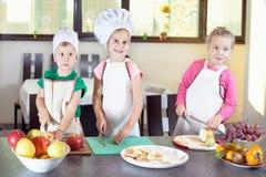 Tres niños lindos están preparando una ensalada de fruta en cocina Fotografía de archivo libre de regalías