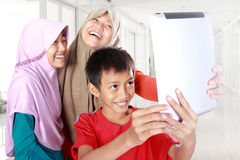 Tres niños musulmanes que juegan la tableta Imagen de archivo