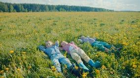 Tres niños pequeños están mintiendo en la hierba y están mirando las nubes en el cielo después del juego Foto de archivo libre de regalías