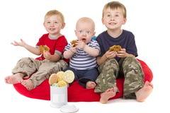 Tres niños pequeños gozan el comer de la galleta imagen de archivo libre de regalías