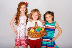 Tres niños preciosos en un fondo blanco, el muchacho están sosteniendo una cesta con imagen de archivo