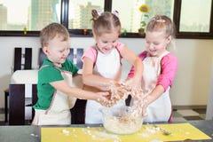 Tres niños preciosos que preparan una torta Foto de archivo libre de regalías