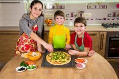 Tres niños que añaden los ingredientes a la pizza cruda Foto de archivo